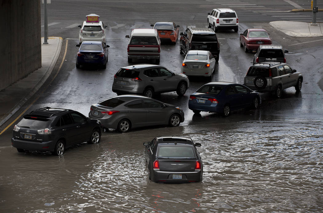 Drivers attempt to navigate a flooded area, where a car is already stuck in the water, near the intersection of Dean Martin Drive and West Twain Ave on Friday, Aug. 4, 2017, in Las Vegas. Bridget  ...