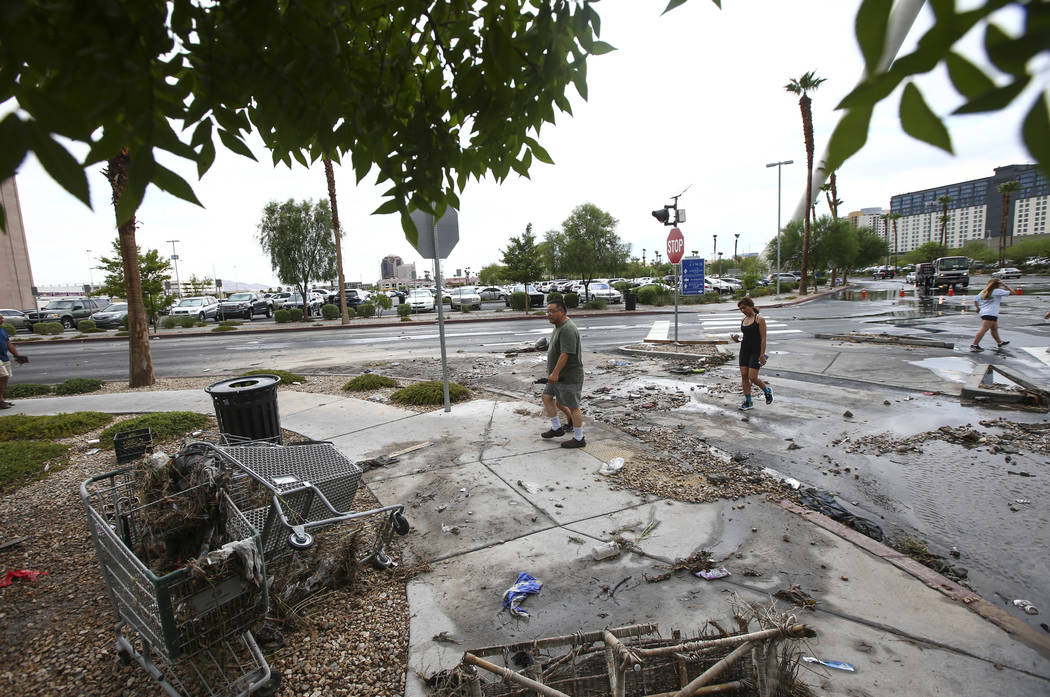 People pass by debris near the wash behind The Linq Hotel in Las Vegas on Friday, Aug. 4, 2017. Six people were rescued from the wash. Chase Stevens Las Vegas Review-Journal @csstevensphoto