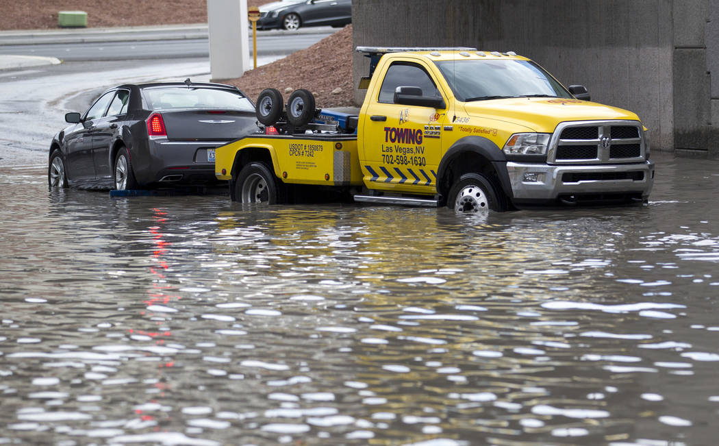 A tow truck pulls a vehicle from flood waters on West Twain Avenue near Dean Martin Drive following rain fall on Friday, August 4, 2017, in Las Vegas. Richard Brian Las Vegas Review-Journal @vegas ...