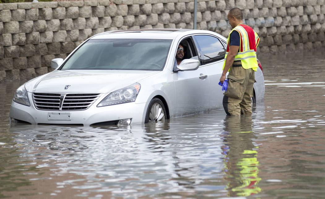 A firefighter talks to a man stalled in flood waters on West Twain Avenue near Dean Martin Drive during a heavy rain fall on Friday, August 4, 2017, in Las Vegas. Richard Brian Las Vegas Review-Jo ...