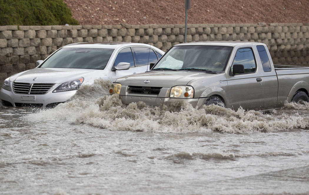 A truck makes its way past a vehicle stalled in flood waters on West Twain Avenue near Dean Martin Drive following rain fall on Friday, August 4, 2017, in Las Vegas. Richard Brian Las Vegas Review ...
