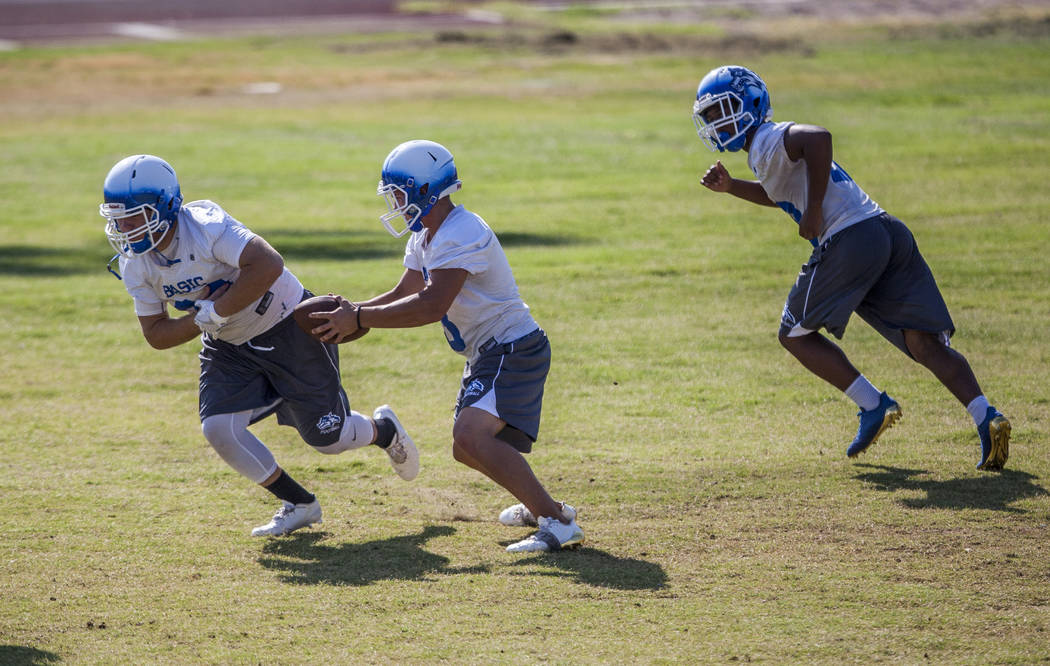 Basic quarterback Paul Myro fakes a handoff to junior Trace Evans, left, while junior Dorian McAllister runs past during practice at Basic High School football field on Monday, Aug. 7, 2017.  Patr ...