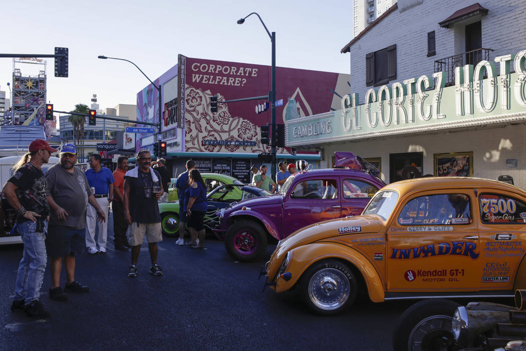 Cliff Cruz, left center, 57, of Las Vegas, answers questions about his 1955 Volkswagen Beetle Drag Race Car, right, and his 1959 Volkswagen Beetle Street car, center, at the Abbey Road Crossing Be ...