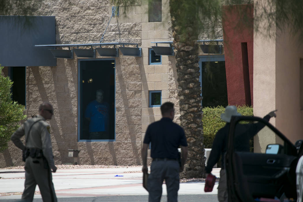 A man looks through a window of the Life Springs Christian Church following an officer involved shooting in the parking lot of the church, Saturday, August 5, 2017, in Las Vegas. Richard Brian Las ...