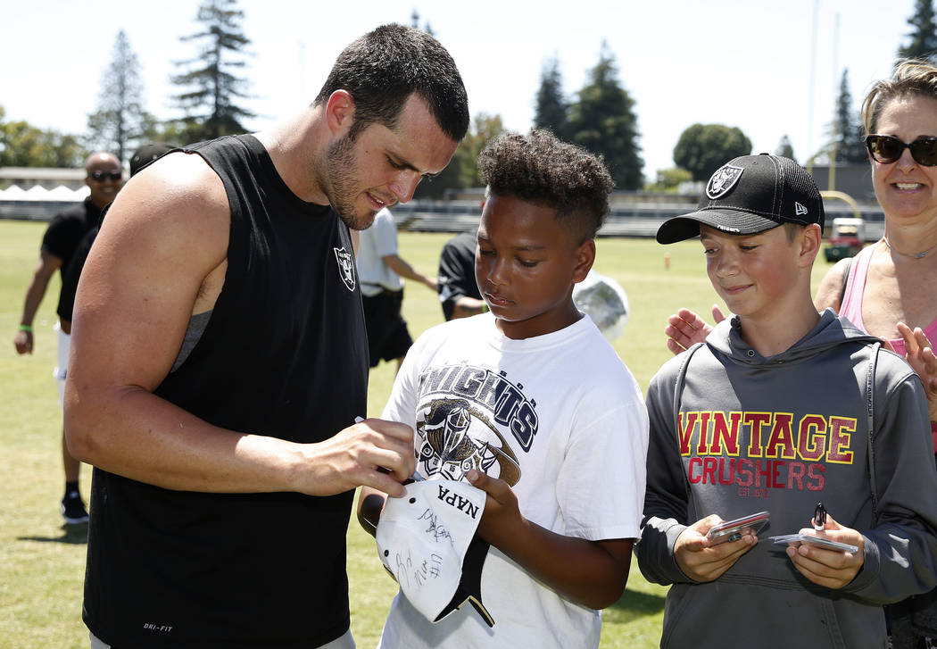 The Oakland Raiders quarterback Derek Carr signs autographs after teams practice at Raiders Napa Valley training complex in Napa, Calif., on Monday, July 31, 2017. Bizuayehu Tesfaye Las Vegas Revi ...