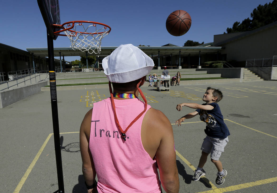 Camp instructor Kris Gambardella watches as camper Wilson shoots baskets at the Bay Area Rainbow Day Camp in El Cerrito, Calif., on Tuesday, July 11, 2017. Gender experts say Rainbow's rapid gro ...