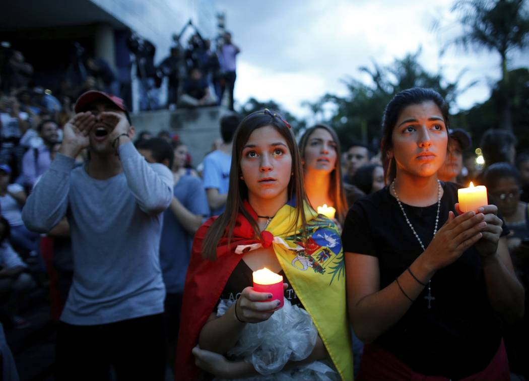 In this Monday, July 31, 2017 photo, anti-government demonstrators attend a candle light vigil in honor of those who have been killed during clashes between security forces and demonstrators in Ca ...