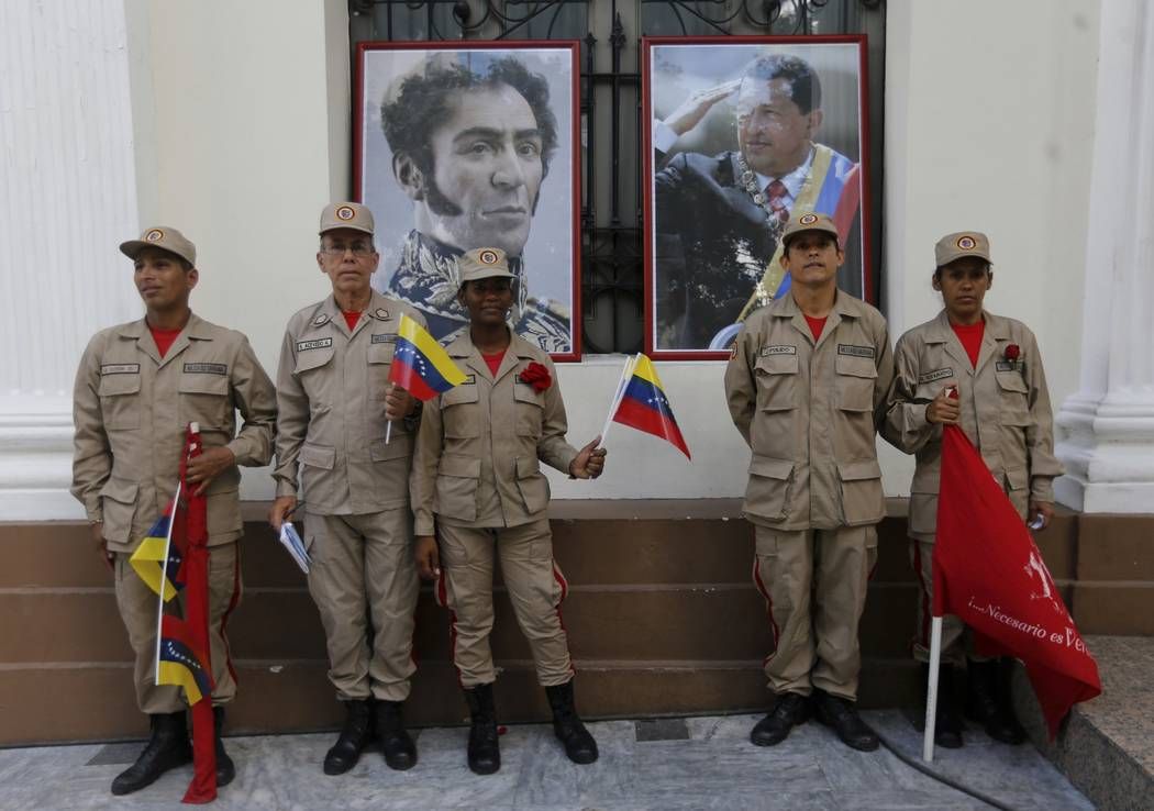 In this Friday, Aug. 4, 2017 photo, militia members pose for a photo next to images of Venezuelan independence hero Simon Bolivar, left, and late President Hugo Chavez outside the National Assembl ...