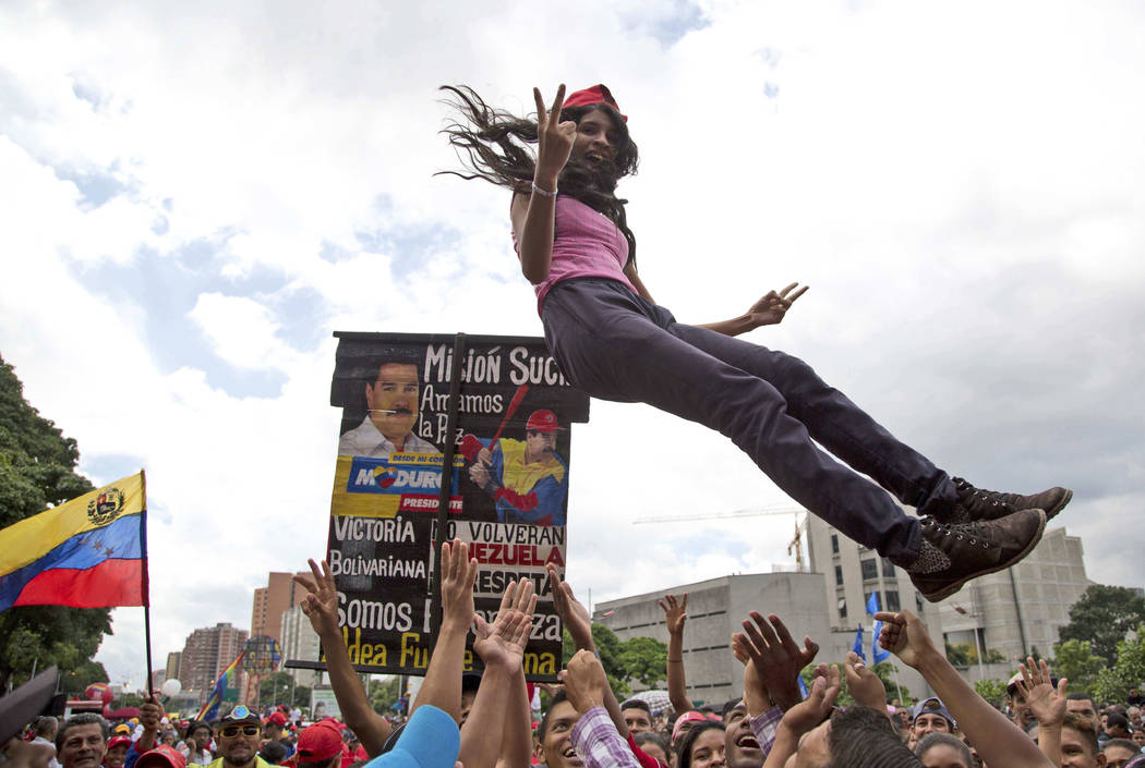In this Friday, Aug. 4, 2017 photo, a young supporter of Venezuela's President Nicolas Maduro is tossed into the air before the start of a march to the National Assembly for the swearing-in ceremo ...