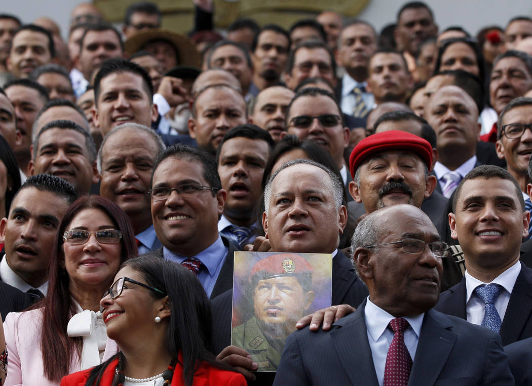 In this  Friday, Aug. 4, 2017 photo, Venezuela's Constitutional Assembly member Diosdado Cabello holds an image of Venezuela's late President Hugo Chavez as delegates including first lady Cilia Fl ...
