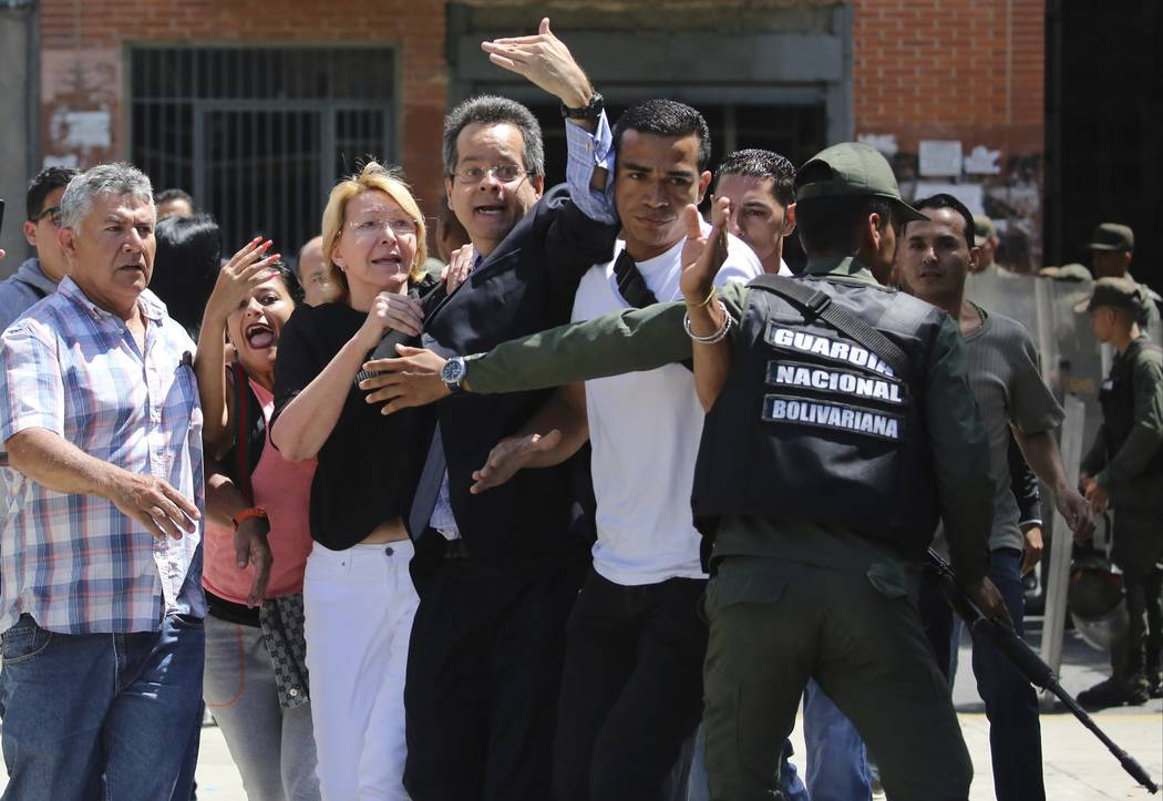 In this Saturday, Aug. 5, 2017 photo, Venezuela's Chief Prosecutor Luisa Ortega Diaz, third from left, is surrounded by loyal employees of the General Prosecutor's office, as she is barred by secu ...
