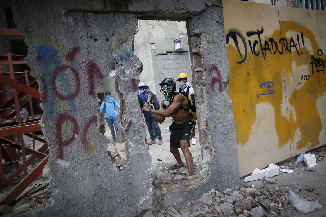 In this Friday, Aug. 4, 2017 photo, a masked anti-government demonstrator breaks down a wall to release pieces of concrete to throw at Bolivarian National Police during a protest against the insta ...