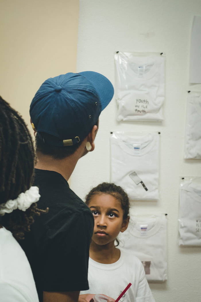 Visitors looking at Kumei Norwood's t-shirt and zine display on July 29, 2017 at The Bakery inside Downtown Spaces, 1800 S. Industrial Road. (Courtesy of Joshua Wheat)