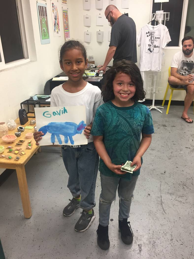 Kumei Norwood, 9, holds up painting by the youngest exhibitor, 6-year-old Gavin Perez, at the zine pop up gallery on July 29, 2017 at The Bakery inside Downtown Spaces, 1800 S. Industrial Road. (C ...