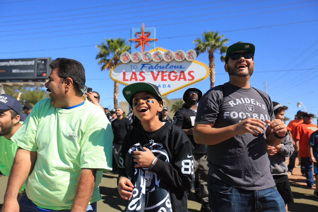 Fans wait to catch mini footballs being thrown out at the Raiders draft party at the Las Vegas sign on Saturday, April 29, 2017. Brett Le Blanc/Las Vegas Review-Journal @bleblancphoto