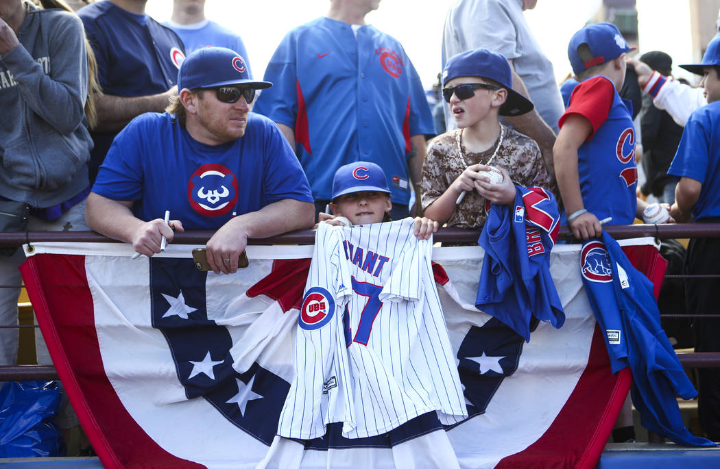 Barry Sorenson, left, waits with children Ashlynn, 10, center, and Hudson, 8, before the Big League Weekend baseball game between the Chicago Cubs and the Cincinnati Reds at Cashman Field in Las V ...