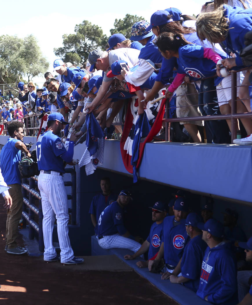 Chicago Cubs' Kris Bryant (17) signs autographs for fans before playing the Cincinnati Reds in the Big League Weekend baseball game at Cashman Field in Las Vegas on Saturday, March 25, 2017. (Chas ...