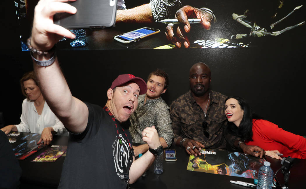 A fan takes a selfie with Finn Jones, Mike Colter and Krysten Ritter during an autograpgh signing on the convention floor at Comic-Con in San Diego. (Eric Charbonneau)
