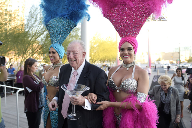 Former Las Vegas Mayor Oscar Goodman is escorted by showgirls Jennifer Johnson, left, and Porsha Viger during the dedication of Oscar B. Goodman Plaza in front of Las Vegas City Hall Wednesday, Oc ...