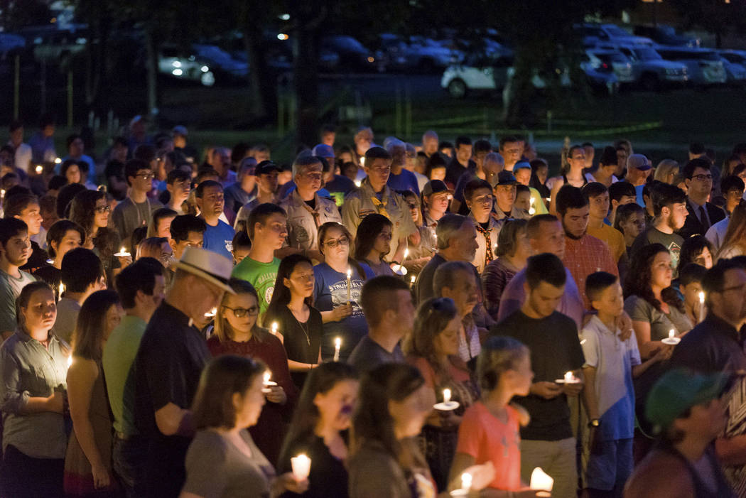 Hundreds from Hallsville, Texas, and surrounding communities gather for a candlelight vigil Sunday, Aug. 6, 2017, after two Hallsville Boy Scouts were killed in a Saturday boating accident. A thir ...