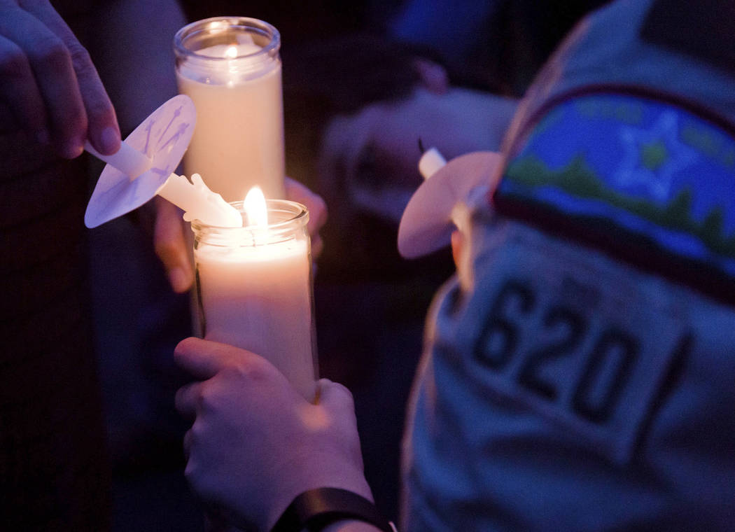 Participants light candles during a candlelight vigil Sunday, Aug. 6, 2017, in Hallsville, Texas, for two Boy Scouts who were killed in a Saturday boating accident. A third scout died Monday. (Les ...