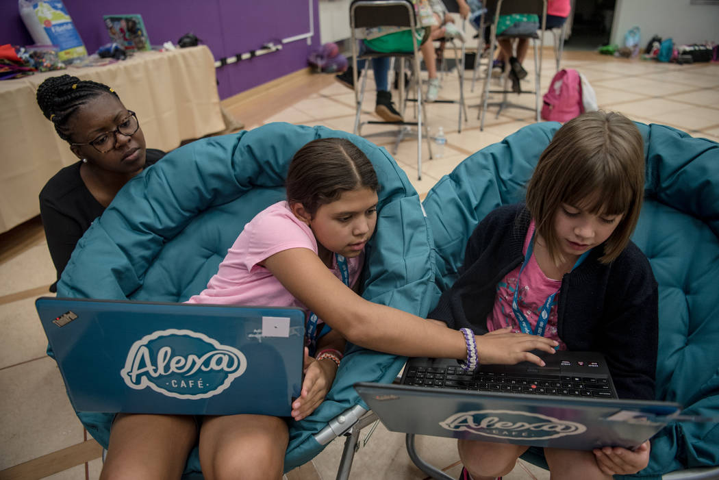 Emily, 9, center, and Triniti, 9, right, work on video game development with STEM Director of Southern Nevada Britney Davis, left, during Alexa Cafe, an all-girls tech camp, at the Girl Scouts of  ...