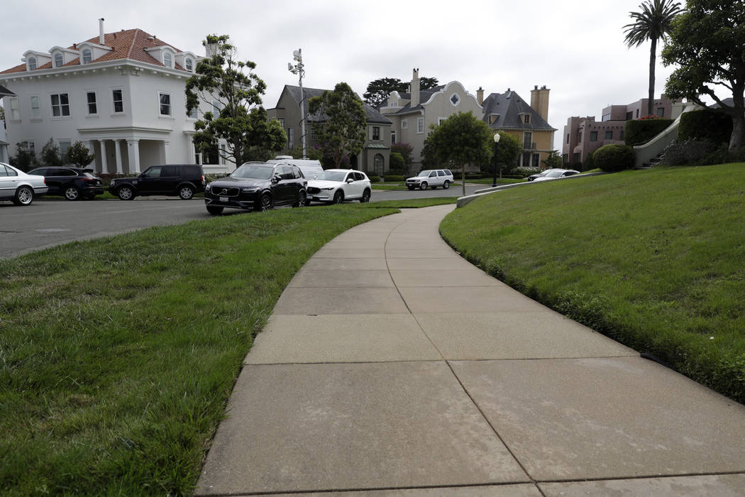 A sidewalk leads into luxury homes in the Presidio Terrace neighborhood, Monday, Aug. 7, 2017, in San Francisco. Thanks to a city auction stemming from an unpaid tax bill, a Bay Area real state in ...