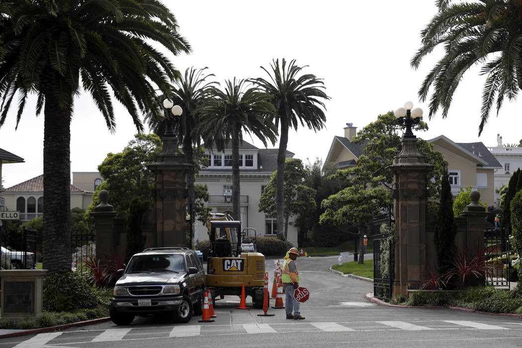 A construction workers stands in front of a gate leading into the Presidio Terrace neighborhood Monday, Aug. 7, 2017, in San Francisco. Thanks to a city auction stemming from an unpaid tax bill, a ...