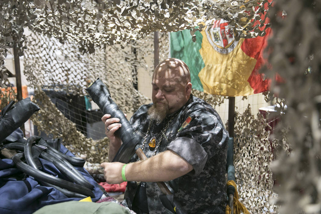 "Elliott  ""General CityBuster"" Sidnam repairs a weapon at The Juggers of the Wasteland tent during Combat Con at Flamingo hotel-casino in Las Vegas, Saturday, Aug. 12, 2017. The J ..."