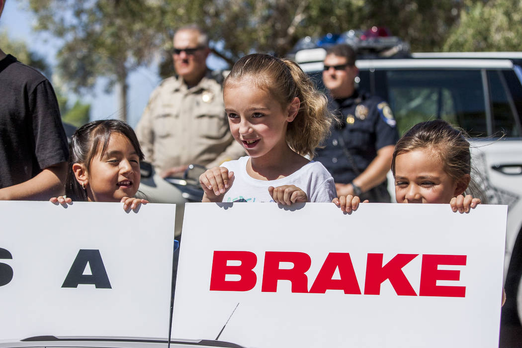 "Hal Smith Elementary School students, from left, Emma Hernandez, Haylee Bartholomew and Lillian Schwartz hold a sign that reads ""Give Us a Brake"" during a news conference about back-to-school safe ..."