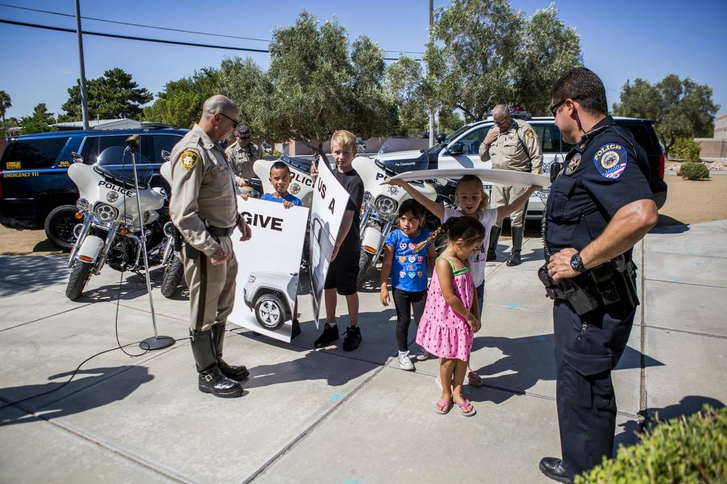 "Metropolitan Police Department Lt. David Jacoby, left, talks with students after they held up a sign reading ""Give Us a Brake"" during a news conference about back-to-school safety at Hal Smith Ele ..."