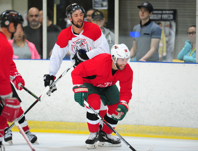 Jason Zucker (red) of the Minnesota Wild and Deryk Engelland of the Calgary Flames battle for the puck during a Las Vegas Firefighters Youth Hockey Foundation charity hockey game at Sobe Ice Arena ...