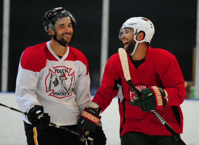 Jason Zucker (red) of the Minnesota Wild and Deryk Engelland of the Calgary Flames share a laugh after a Las Vegas Firefighters Youth Hockey Foundation charity hockey game at Sobe Ice Arena in Nor ...