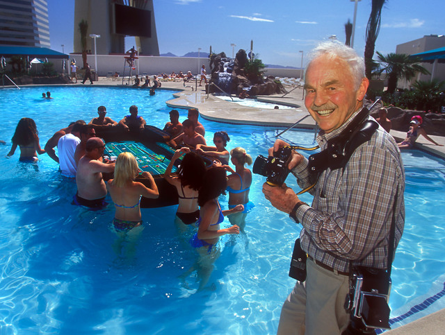 Don English, carrying Hasselblad and Nikon cameras, stands on the new recreation deck, poolside at the Stratosphere hotel-casino in Las Vegas, April 18, 2006. English, who retired from the Las Veg ...