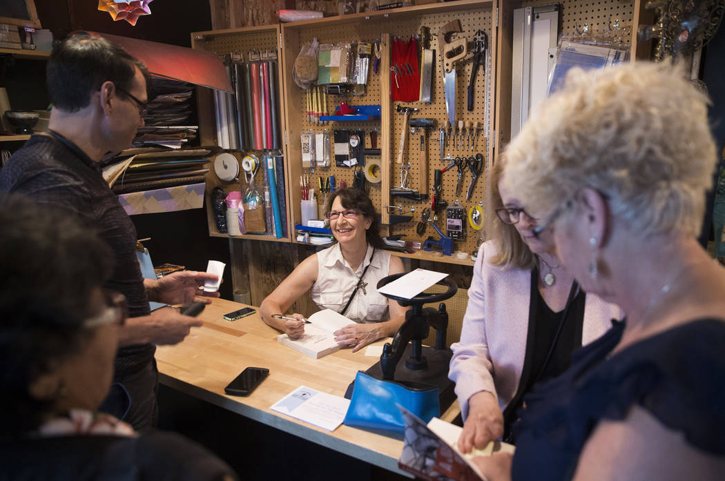 """Las Vegas writer H.G. McKinnis signs books during a party to celebrate her first novel, """"A Justified Bitch,"""" at the Writer's Block on Tuesday, Aug 8, 2017, in Las Vegas. Benjamin Hager Las Vegas R ..."""