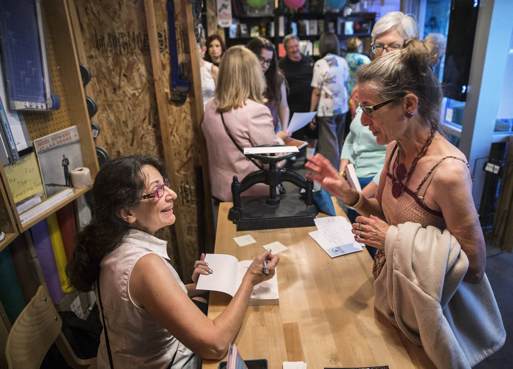 """Las Vegas writer H.G. McKinnis, left, signs books during a party to celebrate her first novel, """"A Justified Bitch,"""" at the Writer's Block on Tuesday, Aug 8, 2017, in Las Vegas. Benjamin Hager Las  ..."""