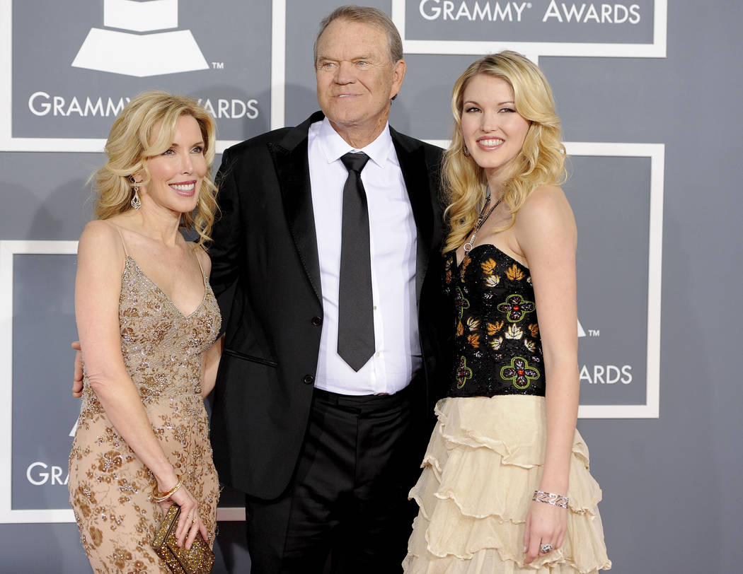FILE - In this Feb. 12, 2012 file photo, Glen Campbell, center, Kim Woolen, left, and Ashley Campbell arrive at the 54th annual Grammy Awards in Los Angeles. Campbell, the grinning, high-pitched e ...