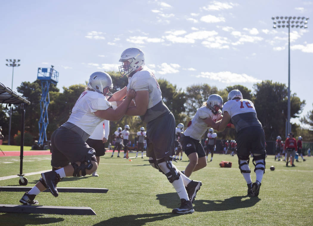 UNLV offensive left tackle Michael Chevalier (77), left,  and  OL Kyle Saxelid (76) participate in drills during football practice at UNLV's Rebel Park in Las Vegas, Tuesday, Aug. 22, 2017. Elizab ...