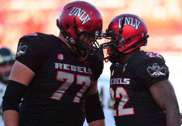UNLV Rebels running back David Greene (22) celebrates with offensive lineman Michael Chevalier (77) after scoring a touchdown while being wrapped against Colorado State in the second half of their ...