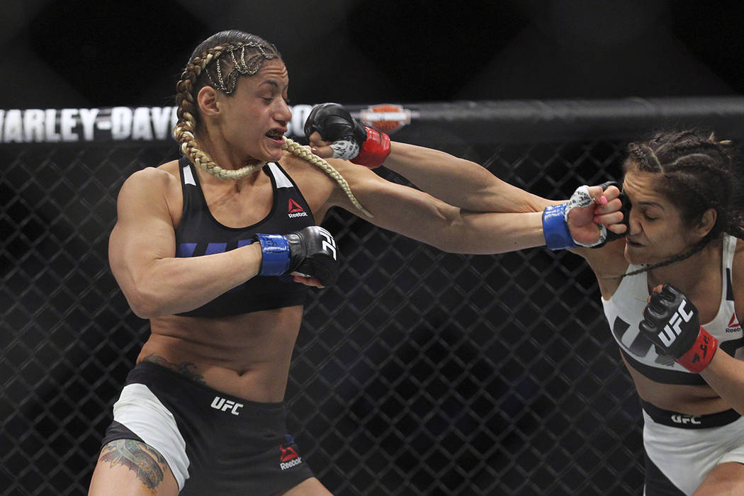 Pearl Gonzalez lands a punch against Cynthia Calvillo during a strawweight mixed martial arts bout at UFC 210, Saturday, April 8, 2017, in Buffalo, N.Y. (AP Photo/Jeffrey T. Barnes)