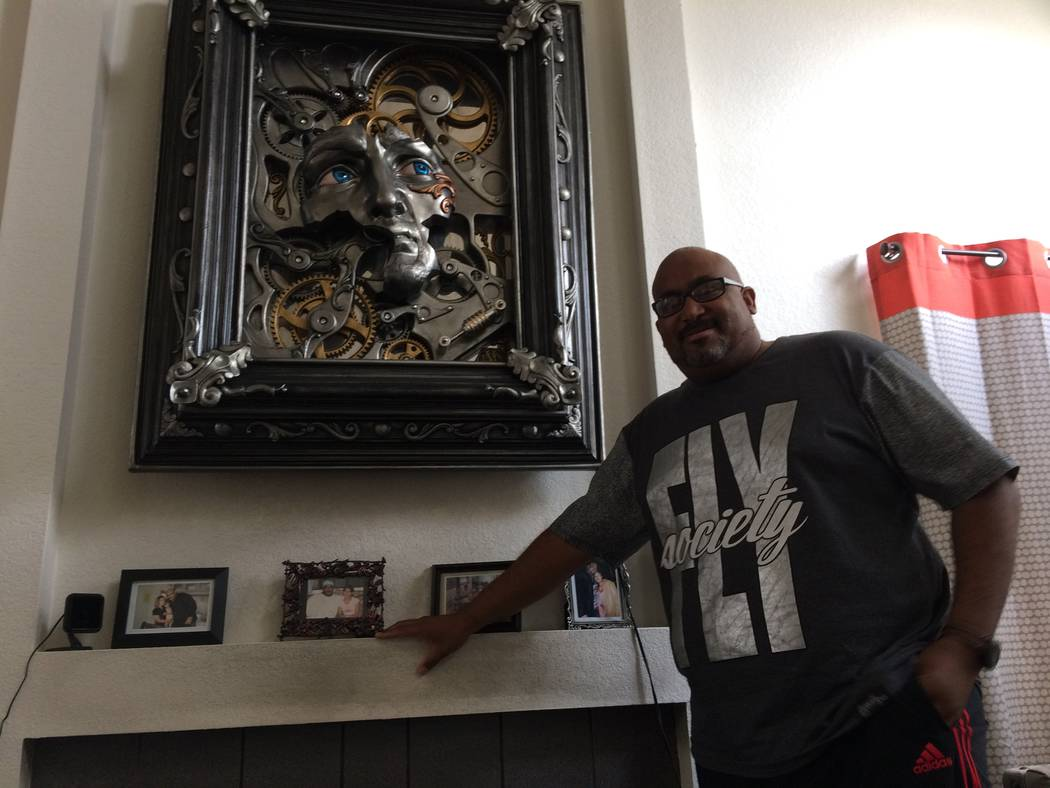 "Dale Mathis talks about his road from carpenter to artist July 25, 2017, in his Desert Shores home. The piece above the fireplace is named ""David,"" which was inspired by Michelangelo's statu ..."