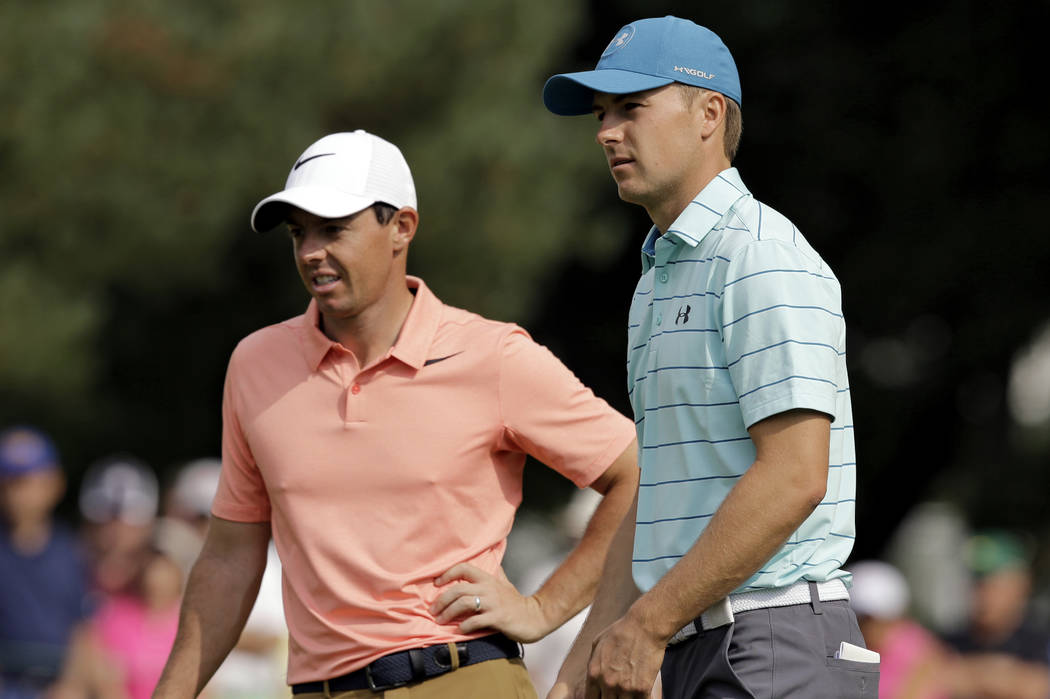 Jordan Spieth, right, talks with Rory McIlroy, from Northern Ireland, on the first hole during the second round of the Bridgestone Invitational golf tournament at Firestone Country Club, Friday, A ...