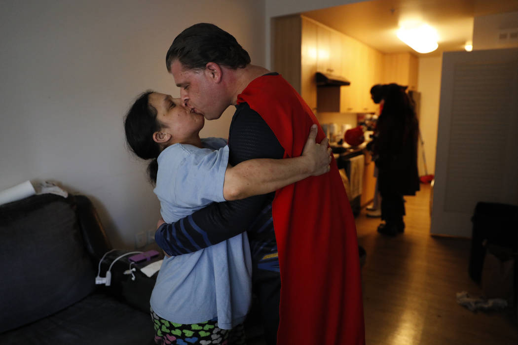 Wearing a Superman costume, Justin Harrison kisses his wife, Hope, in their apartment before heading out to Hollywood Boulevard in downtown Los Angeles on Tuesday, May 16, 2017. Harrison said they ...