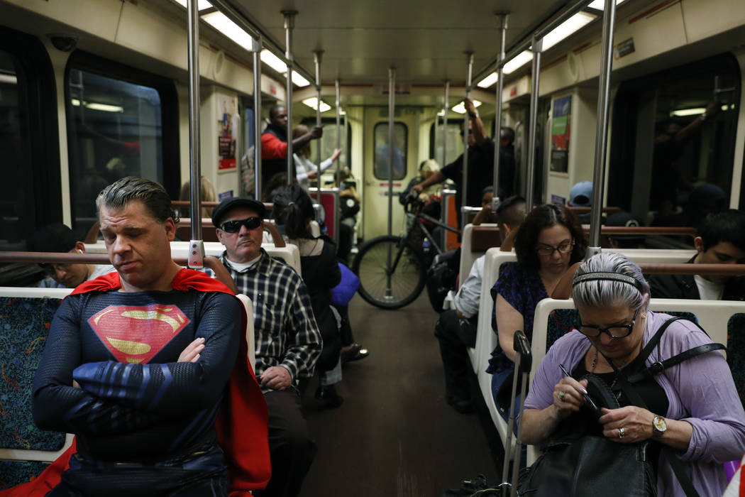 "Superhero impersonator Justin Harrison, left, rides a Metro train wearing a Superman costume on his way to Hollywood Boulevard in Los Angeles on Tuesday, May 16, 2017. ""I always go out in a costum ..."