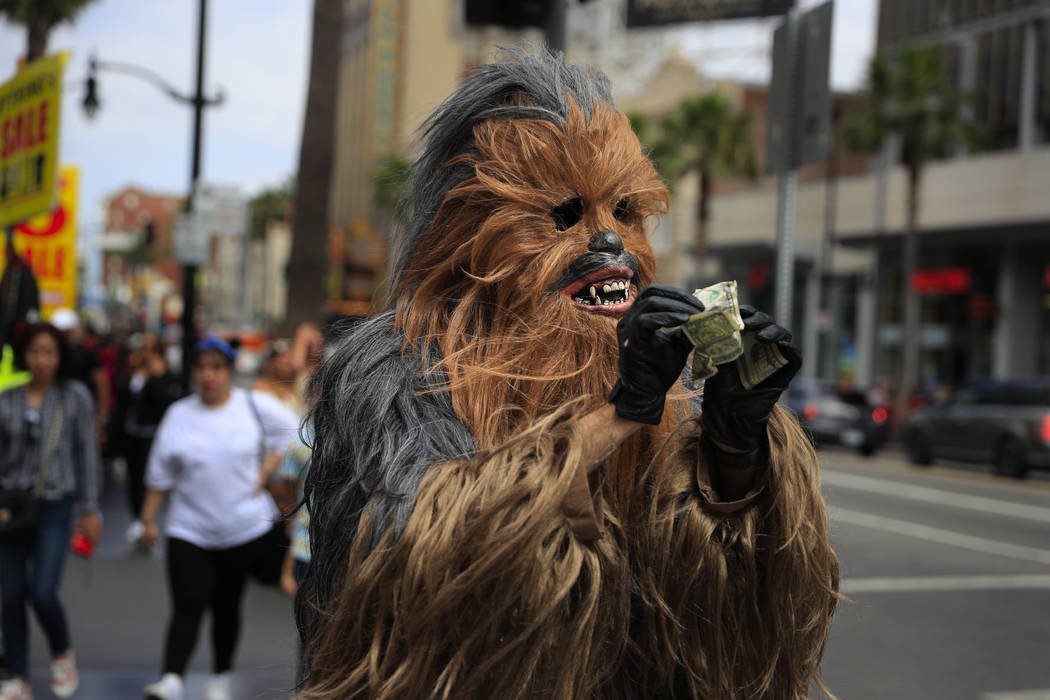 Donte, a musician who only gave his first name, straightens out dollar bills on his first day in a brand new Chewbacca costume purchased from eBay for $441, in the Hollywood section of Los Angeles ...