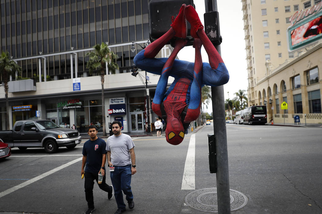 In this Thursday, May 25, 2017 photo, Rashad Rouse, 27, whose dream is getting his star on the Hollywood Walk of Fame, hangs upside down from a traffic signal pole in a Spider-Man costume to get a ...