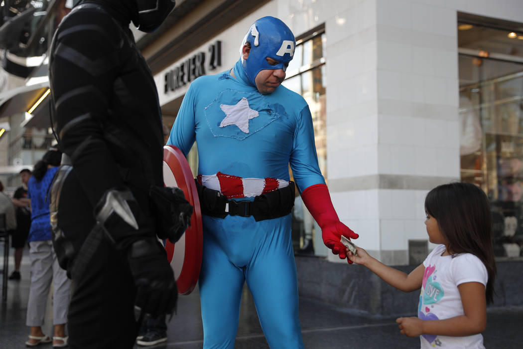 A young tourist tips Justin Harrison, wearing a homemade Captain America costume, and Harrison's roommate, Reginald Jackson in a Black Panther costume after taking pictures with them on Hollywood  ...