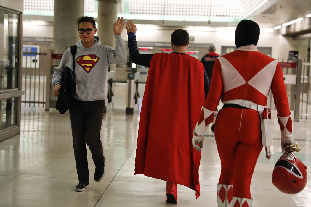 Superman impersonator Justin Harrison, center, high-fives a commuter wearing a sweatshirt with a Superman symbol printed on it as he and his roommate, Reginald Jackson, in a Red Power Ranger costu ...