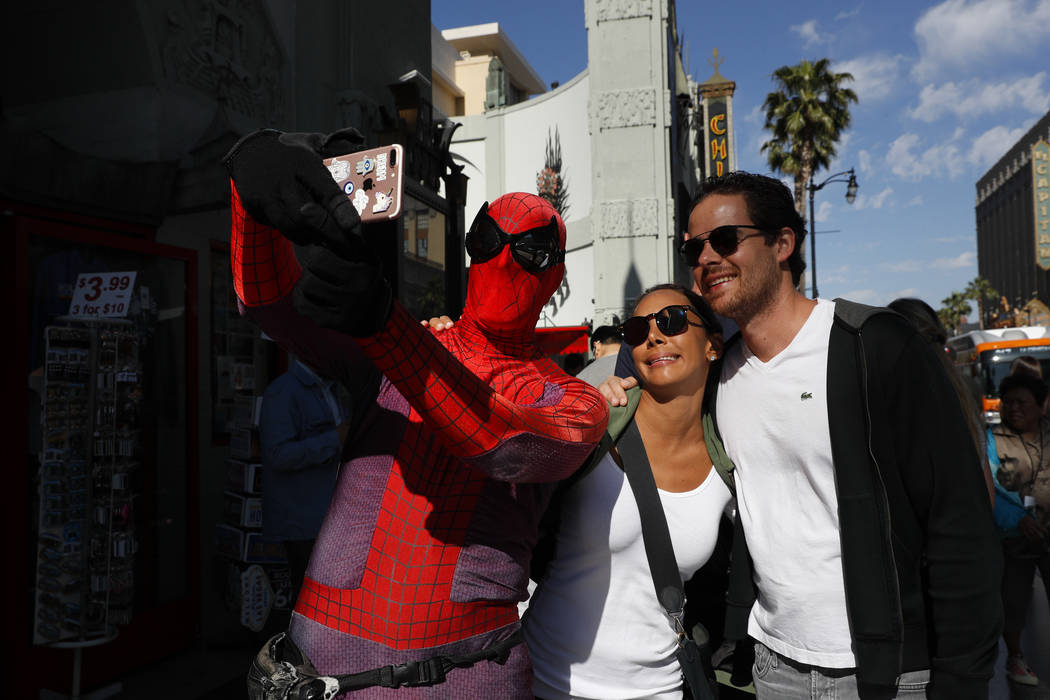 """Superhero impersonator and actor Dan Inigo, left, uses a tourist's smartphone to take a selfie on Hollywood Boulevard in Los Angeles on Wednesday, May 24, 2017. """"It's a place of diversity, it's a  ..."""