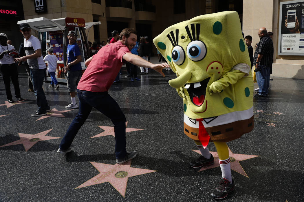 Belnarr Golden, wearing a SpongeBob SquarePants costume, dodges a tourist trying to pull the nose of his costume on Hollywood Boulevard, in Los Angeles on Monday, April 17, 2017. (AP Photo/Jae C.  ...